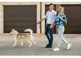 一对年轻时髦的夫妇带着狗在街上散步男人_9699450