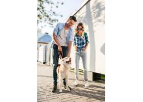 一对年轻时髦的夫妇带着狗在街上散步男人_9699455