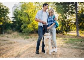 一对年轻时髦的夫妇带着狗在街上散步男女_9699470
