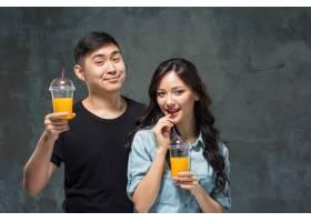 一对年轻漂亮的亚洲夫妇喝着一杯橙汁_9669125