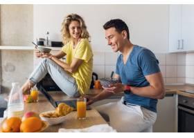 一对年轻迷人的男女早上在厨房一起吃早餐_9699599