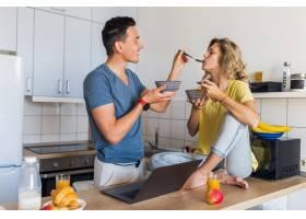 一对年轻迷人的男女相爱早上在厨房一起吃_9699588