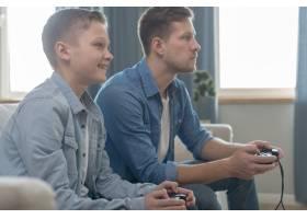 父子俩一起玩电子游戏_7730185
