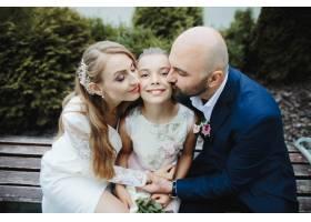 父母亲吻女儿的脸颊_8317043