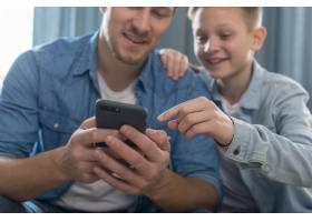 爸爸和可爱的儿子在电话里玩_7733429