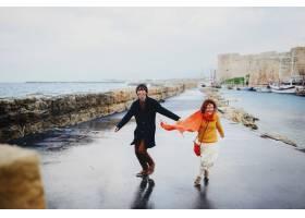 男人和女人在雨中玩得开心空荡荡的海岸_8316801