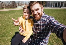 留着胡子的快乐父亲和他的小儿子坐在户外_8074043