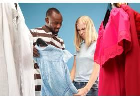 年轻漂亮的女孩在商店选购时一边看衣服一边_8326959