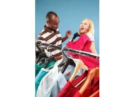 年轻漂亮的女孩在商店选购时一边看衣服一边_8326963