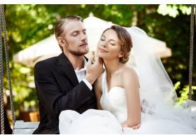 年轻漂亮的新婚夫妇微笑着享受着坐在公_7599795