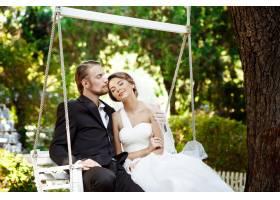 年轻漂亮的新婚夫妇微笑着亲吻着坐在公_7599791