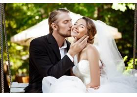 年轻漂亮的新婚夫妇微笑着亲吻着坐在公_7599796