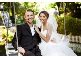 年轻漂亮的新婚夫妇微笑着笑着坐在公园_7599787