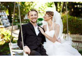 年轻漂亮的新婚夫妇微笑着笑着坐在公园_7599788