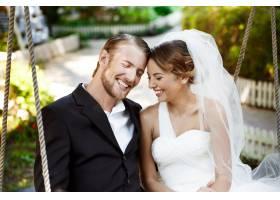 年轻漂亮的新婚夫妇微笑着笑着坐在公园_7599789