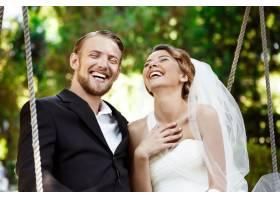 年轻漂亮的新婚夫妇微笑着笑着坐在公园_7599790