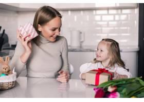 年轻漂亮的母女俩在厨房里放着礼品盒_8471457