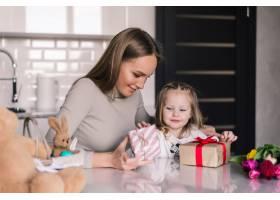 年轻漂亮的母女俩在厨房里放着礼品盒_8471463