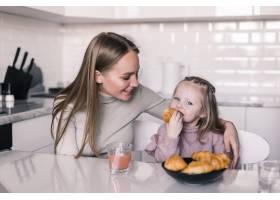 年轻的母女俩在厨房餐桌上吃早餐_8471512
