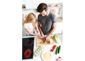 微笑的年轻情侣站在厨房做饭_8078506