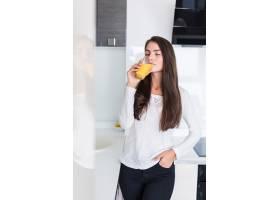 快乐微笑的女人在厨房喝新鲜橙汁的肖像_8471961