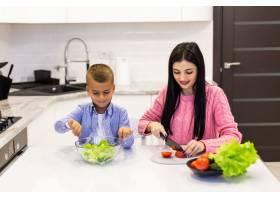 幸福的家庭母亲带着孩子在家准备蔬菜沙拉_8472476
