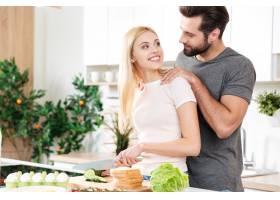 幸福的年轻情侣站在厨房做饭_8078550