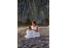 幸福的母女俩坐在一起在日落时分穿着白色_9178936