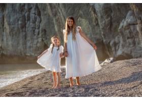 幸福的母女俩身着白色礼服站在日落的海边_9178899