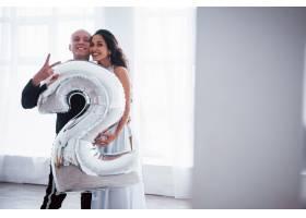 手持2号形状的银色气球穿着奢华服装的年_9125037