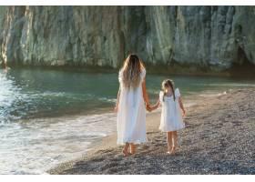 日落时分幸福的母女俩穿着白裙在海边散步_9178928