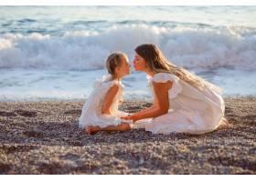 日落时分幸福的母女俩身着白裙坐在一起_9178887