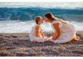 日落时分幸福的母女俩身着白裙坐在一起_9178932