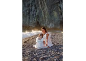 日落时分幸福的母女俩身着白裙坐在海边_9178947