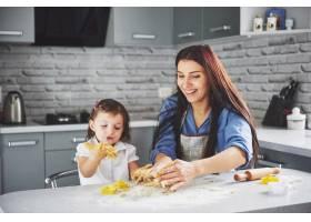 一个漂亮的女儿和她的母亲一起烘焙_9125028