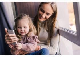 一位美女和她可爱的小女儿正在用智能手机自_8471580