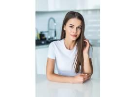 一名年轻女子站在厨房的办公桌旁_8472225