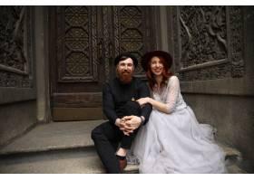 一对不同寻常的婚礼夫妇戴着帽子穿着正式_8316935