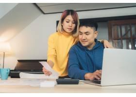 一对年轻的亚洲夫妇在管理财务使用笔记本_3521673