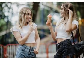 两个戴眼镜的女孩在城市公园舔冰淇淋的肖像_8471677