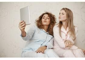 两位美女身着睡衣坐在家中一边用数码平板_8358002