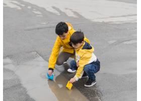 穿着雨衣的年轻人在户外玩耍_9010255