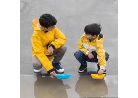 穿着雨衣的年轻人在玩塑料船的前景_9010249