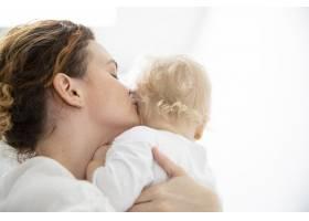 美丽的母亲亲吻她的女儿_7936941