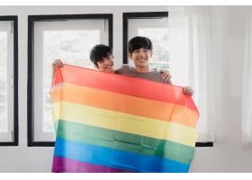 肖像年轻的亚洲同性恋情侣在家中挂彩虹旗感_6136971