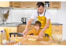 父子俩在厨房里用球拍_7773002