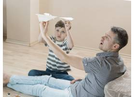 父子俩在室内玩纸飞机_7733430