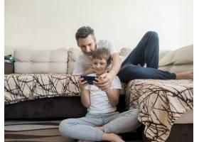 父子俩在手机上玩电子游戏_7748301