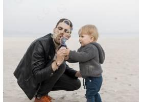 父子俩在海滩上制造肥皂泡_7732317