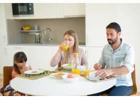 父母和孩子一起吃早餐喝橙汁坐在餐桌前_9988584